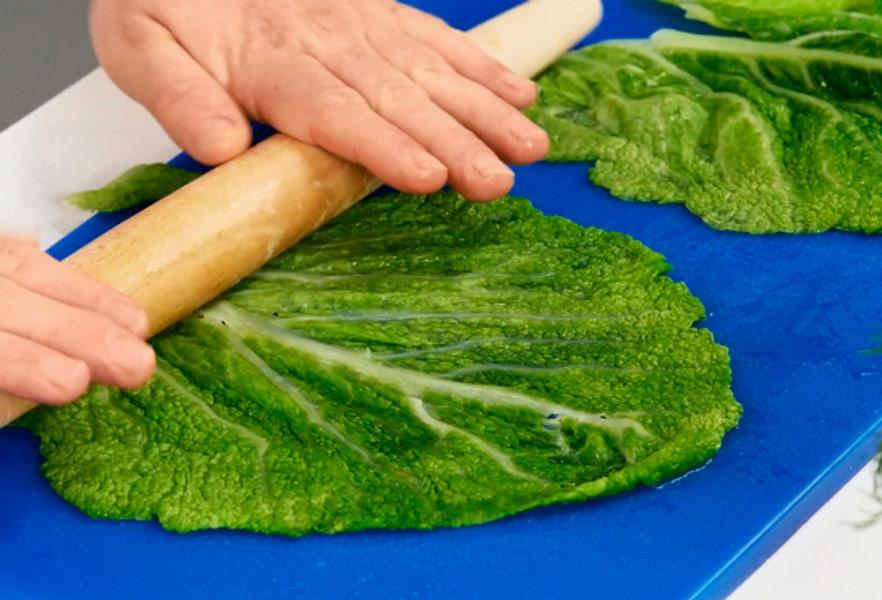 раскатывает скалкой капустные листья