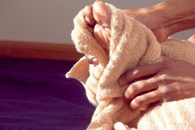 вытирает ноги полотенцем